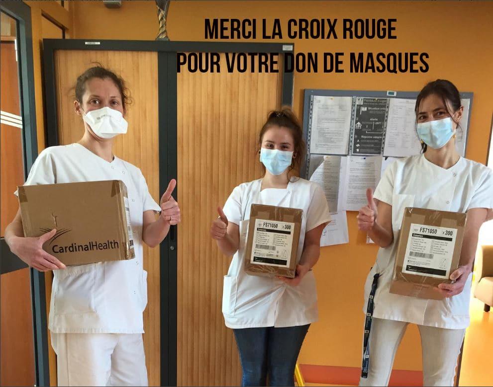 Trois soignantes en blouses blanches et portant des masques de protection portent des cartons de dons de masques et lèvent le pouce en l'air.