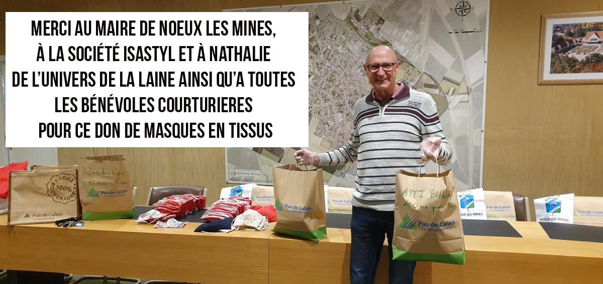 Photo d'un homme qui tient des sacs remplis de dons de masques en tissus.