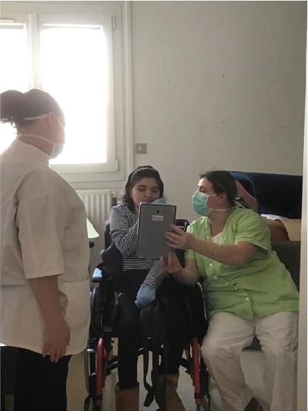 Une jeune fille en situation de handicap en visio avec sa famille, accompagnée par des professionnels