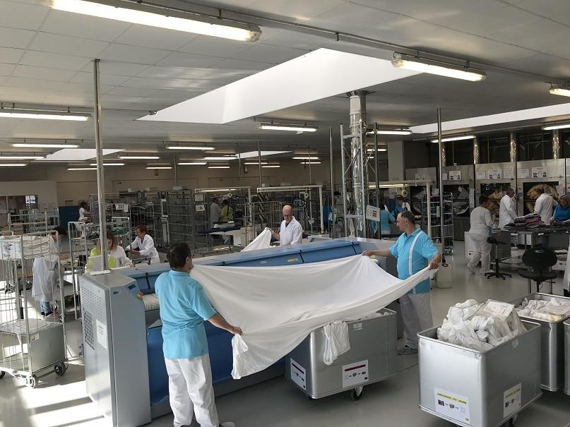 Travailleurs en blanchisserie qui repassent des draps dans une machine.